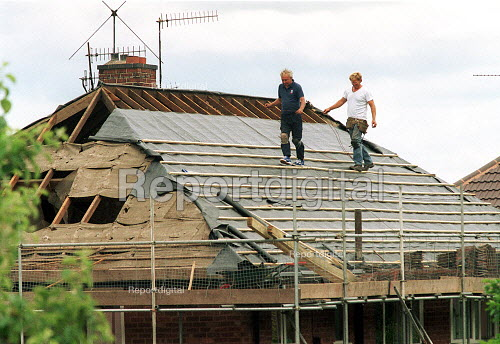 Roofers balancing on rafters whilst replacing roofing tiles on housing. - John Harris - 2001-06-28