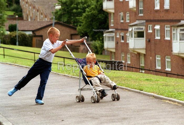 Brother pushing pram on housing estate Birmingham - John Harris - 2001-06-28