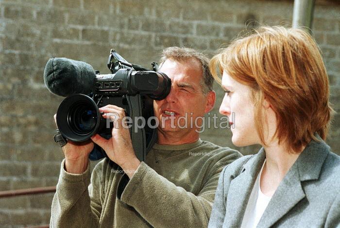 Freelance cameraman filming news. - John Harris - 2001-07-15