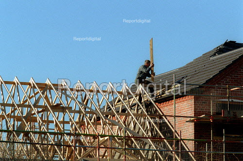 Construction worker placing boards on the roof of a new building. - John Harris - 2002-03-07