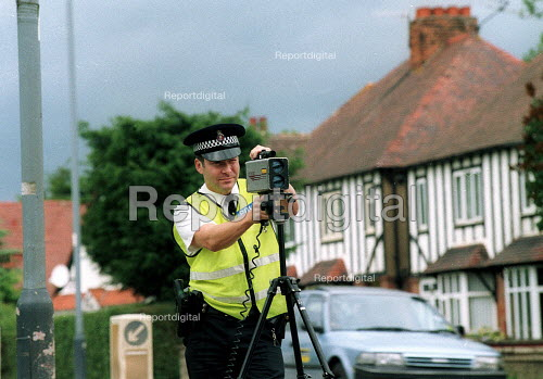 Armed policeman measuring the speed of oncoming vehicles with a handheld laser equiped speed measuring device - John Harris - 2002-07-16
