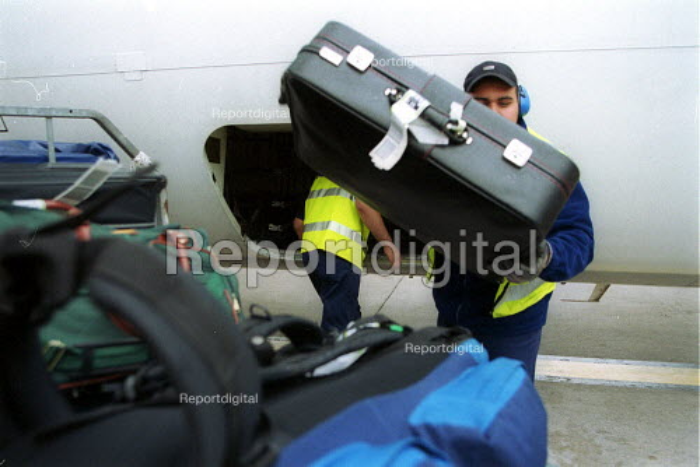 Baggage handlers unloading luggage from airplane at Birmingham International Airport. - John Harris - 2002-08-01