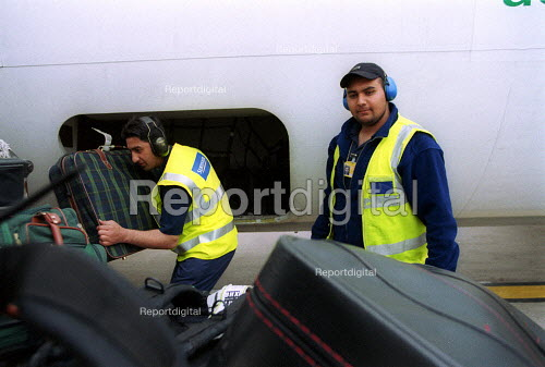 Baggage handlers unloading luggage from airplane at Birmingham International Airport. - John Harris - 2002-08-01