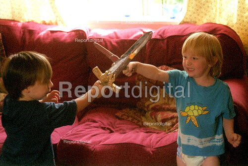 Two boys playing fighting with swords at home. - John Harris - 2002-08-06