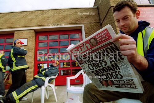 FBU picket reads The Sun newspaper, with a headline - Fire Union chiefs are Saddam Stooges - a story suggesting FBU leaders promoted Saddam Hussein. Firefighters strike picket line. Stratford upon Avon Fire station. - John Harris - 2002-11-15