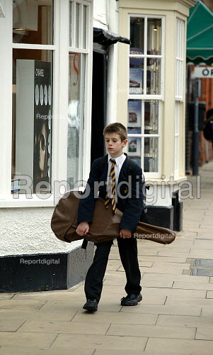 Grammar School pupil walking home from school with his guitar in a guitar case. Stratford on Avon - John Harris - 2003-05-20