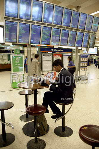 Businessman reading a magazine at a cafe whilst waiting. Birmingham New Street railway station. - John Harris - 2003-05-20