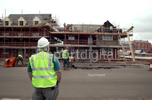 Site manager watching workers building houses on a greenfield building site. Westbury homes - using Space4 prefabricated construction technique. Stratford on Avon Warwickshire. - John Harris - 2003-05-21