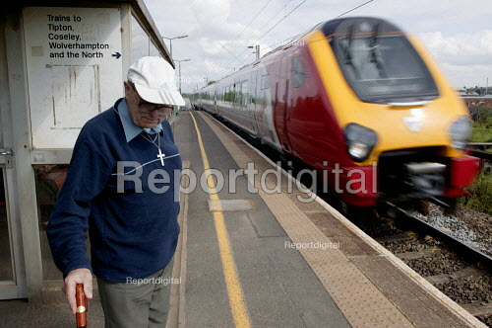 Passenger waiting for a local train as a Virgin intercity express hurtles through Dudley Port railway station. - John Harris - 2003-06-02