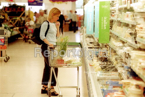 Customer choosing a product from the shelves, Tesco Supermarket. - John Harris - 2002-07-02