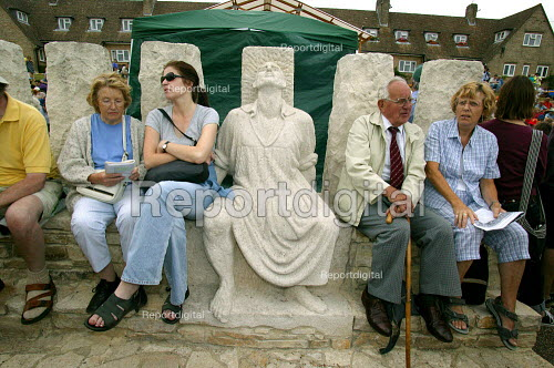 People sitting on the Tolpuddle Martyrs' sculpture by Thompson Dagnall. Tolpuddle Martyrs' Festival Dorset. - John Harris - 2003-07-20