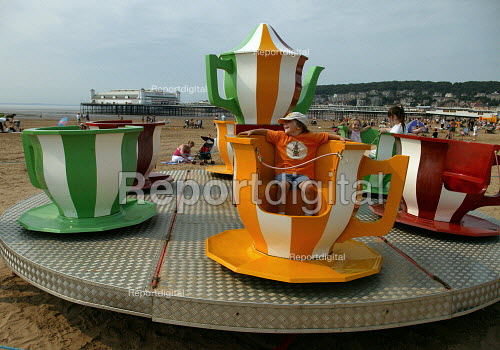 Child riding on a teacup roundabout on the beach Weston Super Mare in the hottest temperatures. - John Harris - 2003-08-04