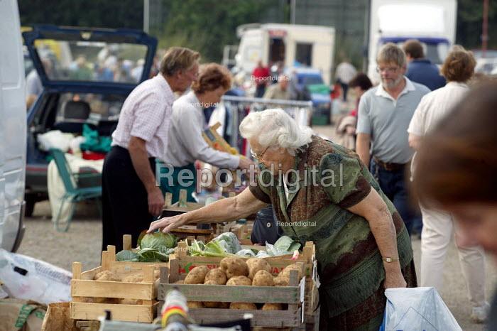 Elderly woman shopping for vegetables. Saturday morning car boot sale, Stratford on Avon, Warwickshire - John Harris - 2003-09-06