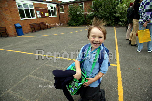 Pupil running out of school into parent's arms in the playground as they are collected from School. - John Harris - 2003-10-03
