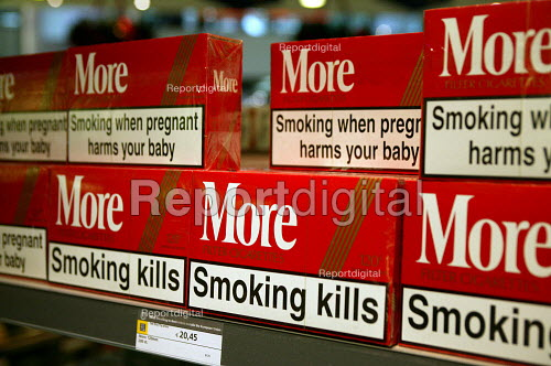 Cartons of duty free More cigarettes with statutory health warning of the dangers of smoking, which increases the risk of fatal heart and lung diseases. Amsterdam Airport. - John Harris - 2003-11-25