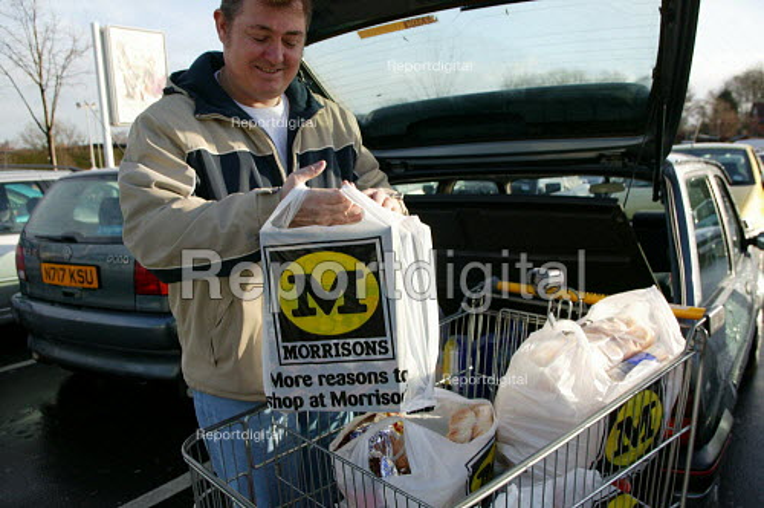 Shopper loading the car at Morrisons Supermarket. - John Harris - 2004-01-09