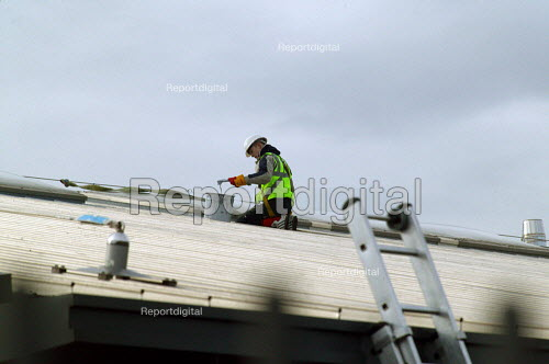 Construction worker with safety harness sealing a roof on a new building. - John Harris - 2004-02-05