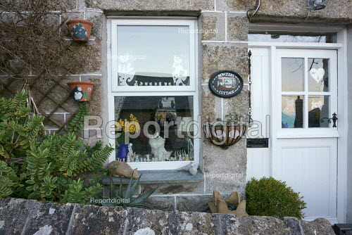 A cat sitting in the window of Mowzers Cottage, Mousehole. A Mousehole cat themed cottage named after The Mousehole Cat, a childrens book, Cornwall - John Harris - 2015-03-21