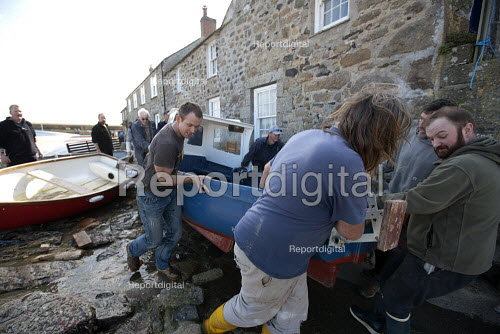Fishermen lifting and carrying small boats. Launching the fishing fleet at the start of the season, Mousehole harbour, Cornwall - John Harris - 2015-03-21