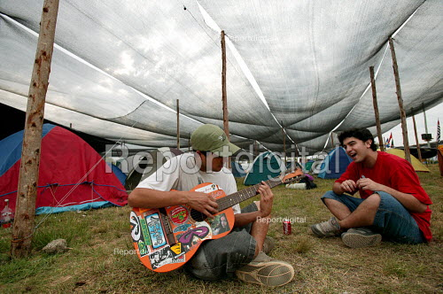 World Social Forum, Porto Alegre Brazil. Delegates sing rebel songs with a guitar in the youth camp. - Jess Hurd - 2005-01-24
