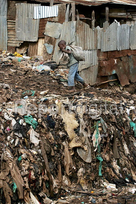 Child makes his way through an open sewer, Kibera slum - the largest slum in Africa. Nairobi, Kenya. - Jess Hurd - 2005-05-04