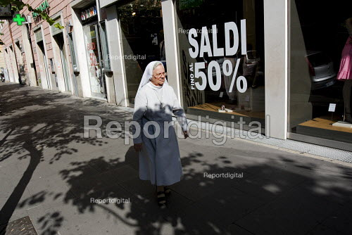 Nun walks past a 50 sale sign in Rome. Italy. - Jess Hurd - 2009-07-08