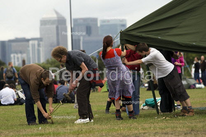 With Canary Wharf behind, Climate Camp protestors establish on Blackheath. South East London. - Jess Hurd - 2009-08-26