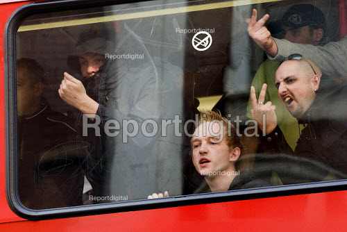 EDL supporters are escorted by the police on a bus out of Birmingham. English Defence League march in Birmingham. Making rude v signs. - Jess Hurd - 2009-09-05