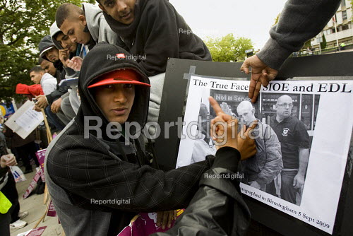 Anti-fascist demonstrators and local muslim youths gathered to counter a threatened march by right wing groups outside Harrow Central Mosque. London. They have a photocopy of our picture of EDL member giving a Nazi salute. - Jess Hurd - 2009-09-11