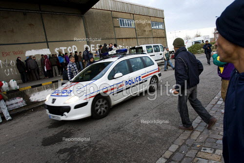Police patrol as refugees in Calais made homeless after the clearing of the Jungle queue for food. France. - Jess Hurd - 2009-10-16