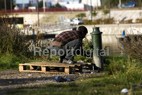 Refugees sleeping rough in Calais are forced to wash at a water pump. France. - Jess Hurd - 2009-10-15