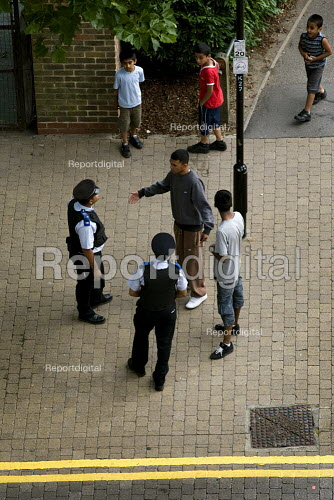 Young Bengali men are issued a Dispersal Order by PCSOs. The order effectively means an enforced curfew for those deemed anti social between 6pm and 4am every day. Tower Hamlets, East London. - Jess Hurd - 2010-07-24