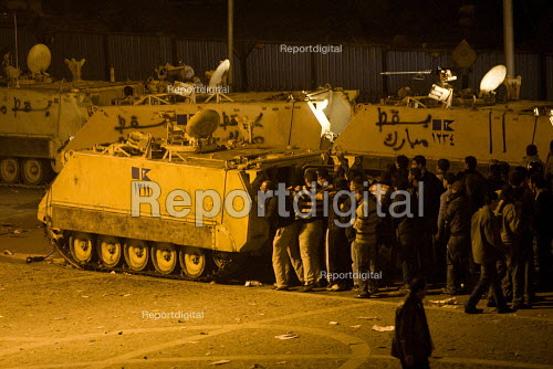 Protestors taking cover behind an amoured vehicle. Uprising on the streets of Cairo against the dictatorship. Egypt. - Jess Hurd - 2011-01-28