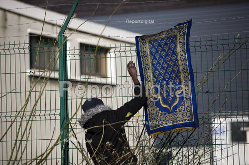Sudanese refugee washing a prayer mat outside a temporary shelter in freezing conditions in Calais. France. - Jess Hurd - 2015-01-13