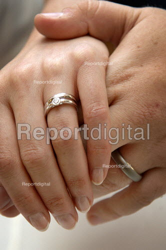 Newly married bride and bridegroom hold hand. Close up shot showing wedding rings. - Paul Carter - 2005-09-17