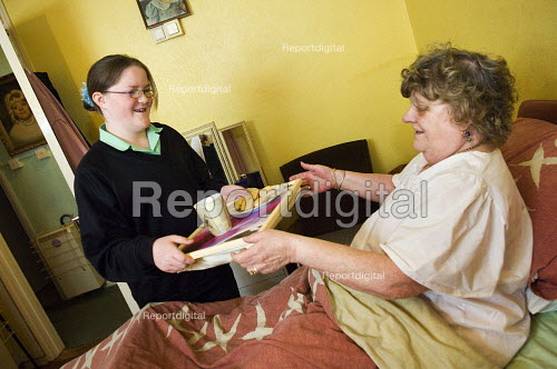 Young girl in school uniform, brings a tray of tea and biscuits to her bedbound grandmother.Young carers looking after elderly relatives. Photo posed by models. Model released. - Paul Carter - 2006-11-14