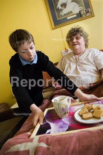 Young boy in school uniform, brings a tray of tea and biscuits to his bedbound grandmother.Young carers looking after elderly relatives. Photo posed by models. Model released. - Paul Carter - 2006-11-14
