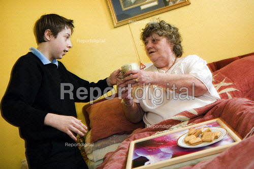 Young boy in school uniform, brings a tray of tea and biscuits to his bed bound grandmother.Young carers looking after elderly relatives. Photo posed by models. Model released. - Paul Carter - 2006-11-14
