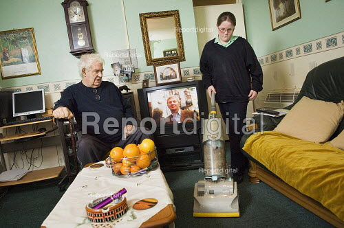 Young girl in her school uniform, hoovers for her grandfather.  Young carers looking after elderly relatives. Photo posed by models. Model released. - Paul Carter - 2006-11-14