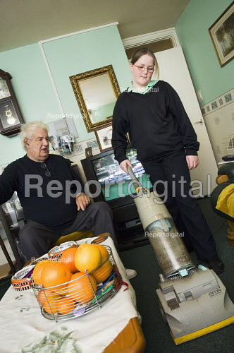 Young girl in her school uniform, hoovers for her grandfather.