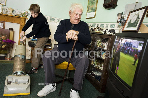Young boy hoovers for his grandfather.  Young carers looking after elderly relatives. Photo posed by models. Model released. - Paul Carter - 2006-11-14