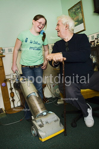 Young girl hoovers for her grandfather.