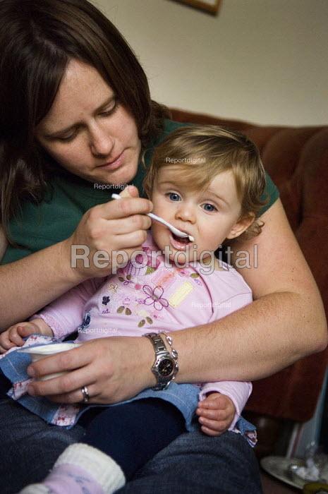 A mother feeding her daughter a yoghurt. - Paul Carter - 2006-11-29