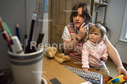 A mother works from home at a computer with her daughter on her lap. - Paul Carter - 2007-02-09