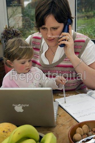 A mother works from home at a laptop with her daughter on her lap. - Paul Carter - 2007-02-09