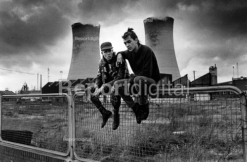 Unemployed youths sitting in front of a demolished factory. Behind are the cooling towers of ICI Billingham, Stockton-on-Tees 1980 - John Sturrock - 1980-10-10