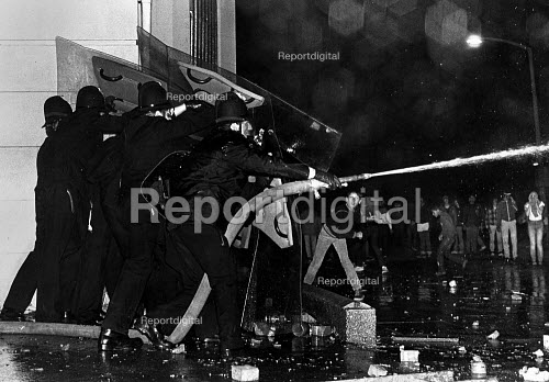 Police improvise with fire hose to hold off rioters, at the Toxteth Riot, in Liverpool. - John Sturrock - 1981-07-05