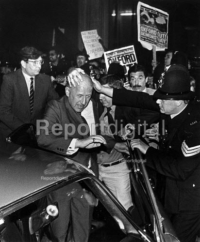 Merseyside Chief Constable Kenneth Oxford is protected by policemen as he leaves a meeting with Community Leaders after the Toxteth riots. Protest by members of Liverpool 8 Defence committee and supporters, Liverpool 1981 - John Sturrock - 1981-08-01