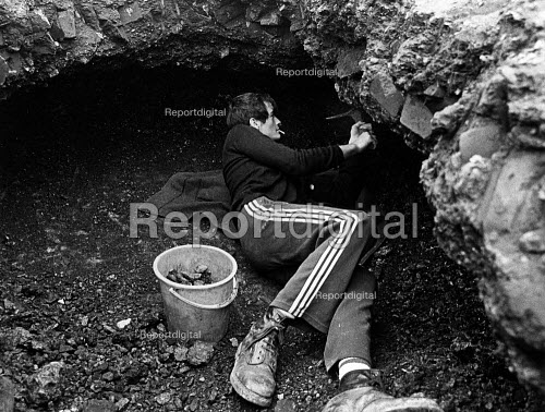 The Miners Strike, Upton near Pontefract. Digging for fragments of coal in the waste tip of a colliery. A youth was killed a few days previously on this tip, when an overhang he was working under collapsed. - John Sturrock - 1984-09-11