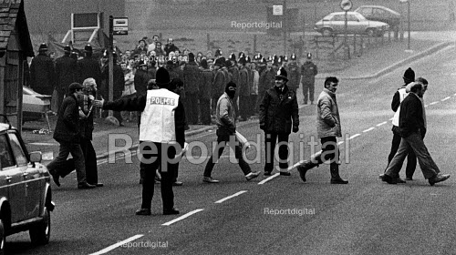 Miners Strike, 25 strike breaking miners leaving Silverwood Colliery (nr Rotherham) at the end of a shift. 150 pickets jeers from behind the police line. - John Sturrock - 1985-02-06